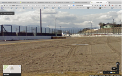 From the gravel trap, outside of Dunlop curve, at the point where the drivers are moving to use the maximum width of the track. Tower 12 visible in background